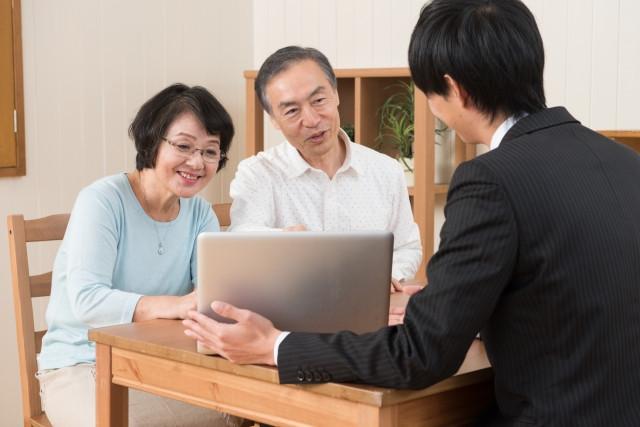 バリアフリーリフォームの説明をする人と話を聞く老夫婦